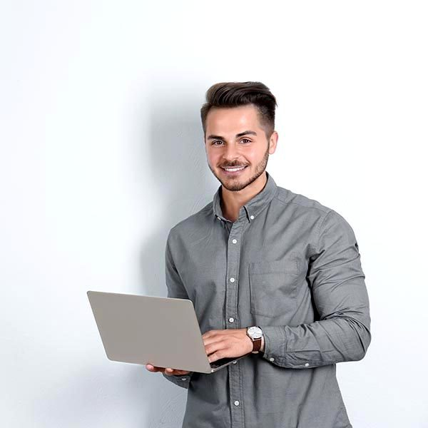 Man in casual clothes with laptop on light background